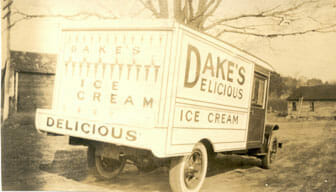 """Bright red Model-T delivery truck with """"Dake's Delicious Ice Cream"""" on the side of it."""