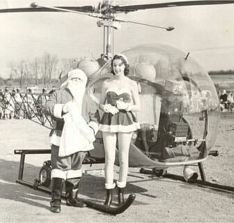 Santa and a woman elf next to a helicopter