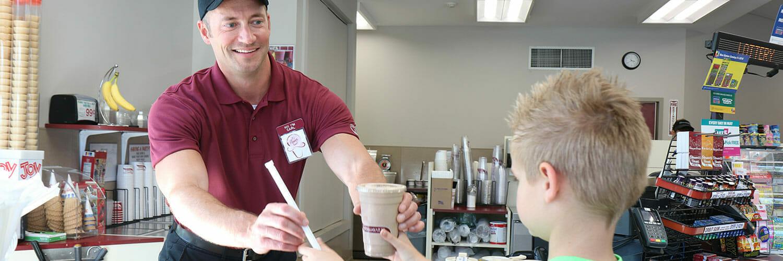 employee handing coffee to a young boy