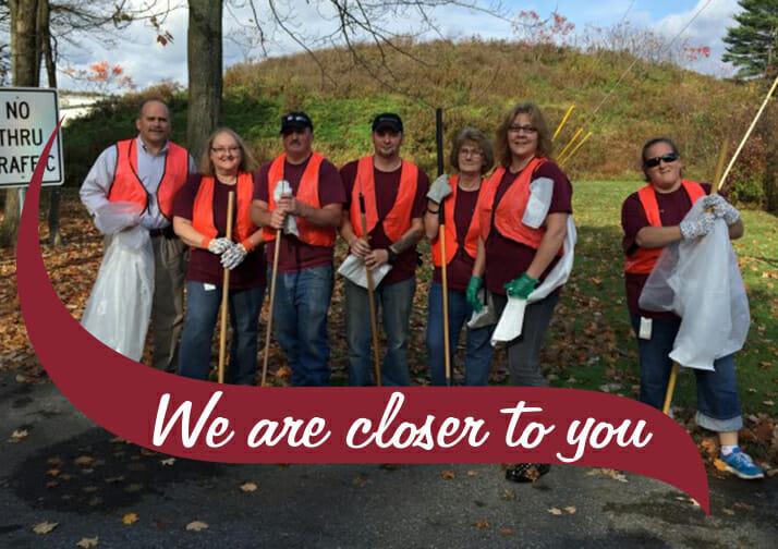 Stewart's employees wearing orange vests cleaning up garbage