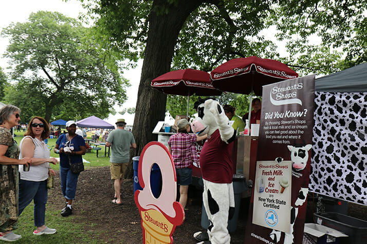 flavor mascot in front of booth welcoming customers