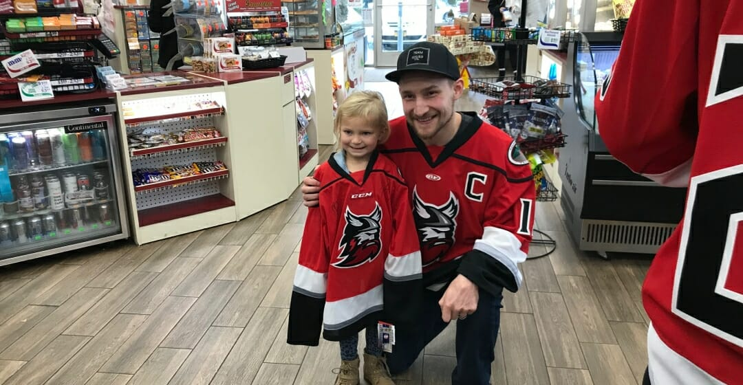 Hockey Player posing with Young fan