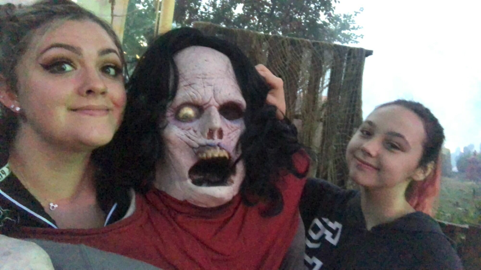 Two girls posing with a zombie