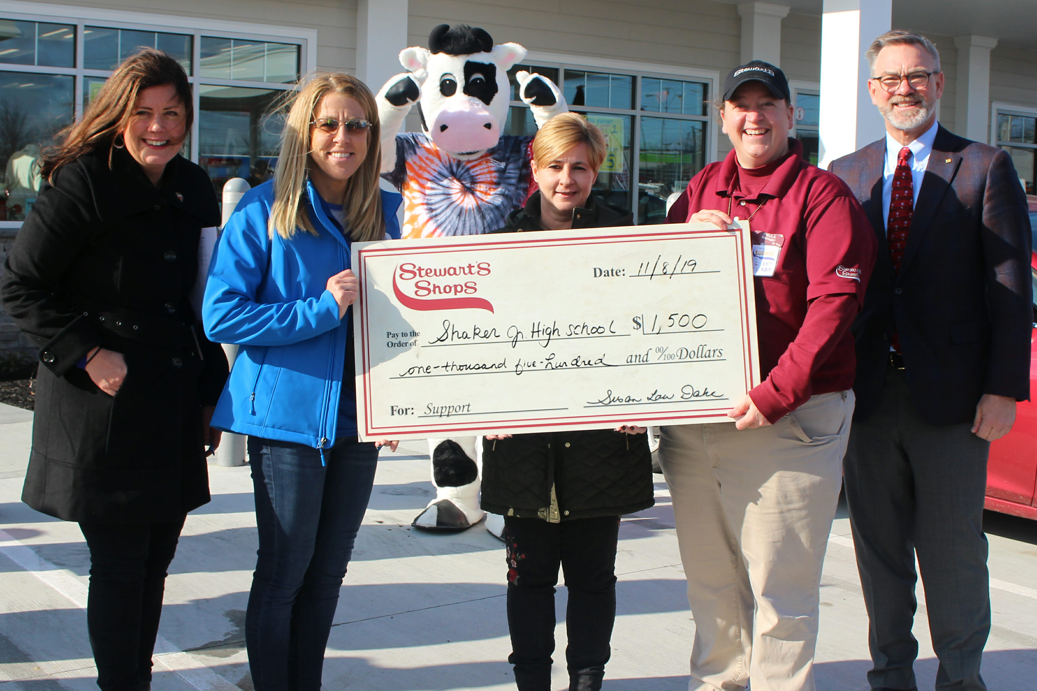 1,500 dollar donation check presentation to the Shaker Jr high school food pantry. 5 people featured in the image