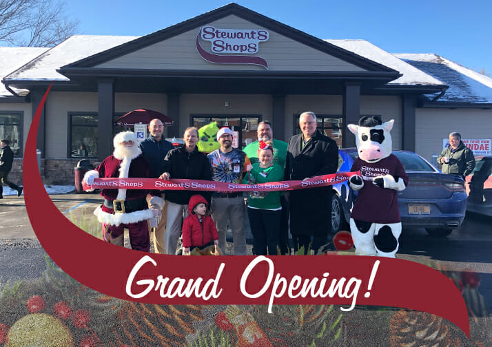 Grand Opening! A group gathered at a ribbon cutting event with a Stewarts shop in the background.
