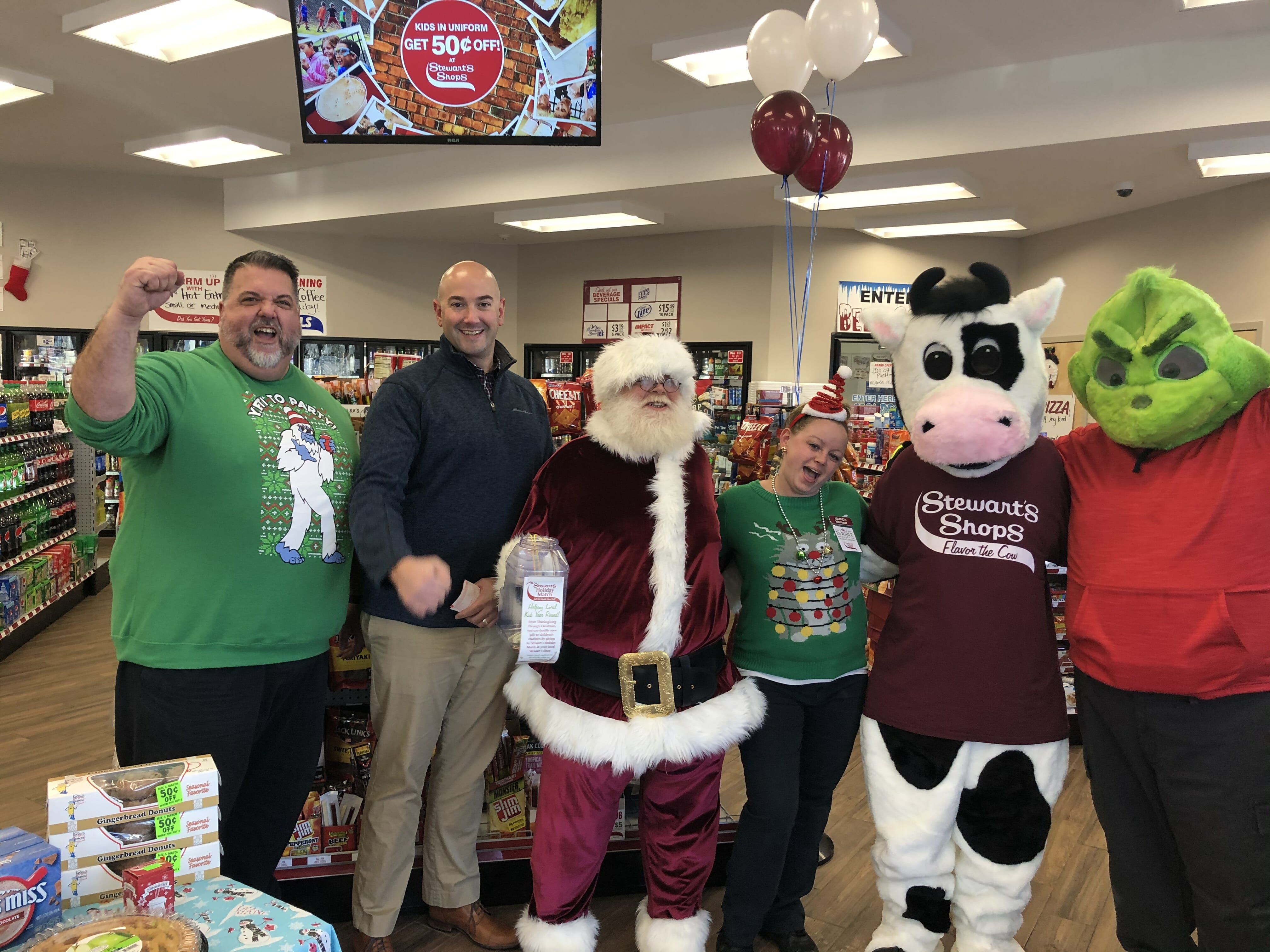 An excited and festive group at the grand opening including santa, a cow, and the Grinch.