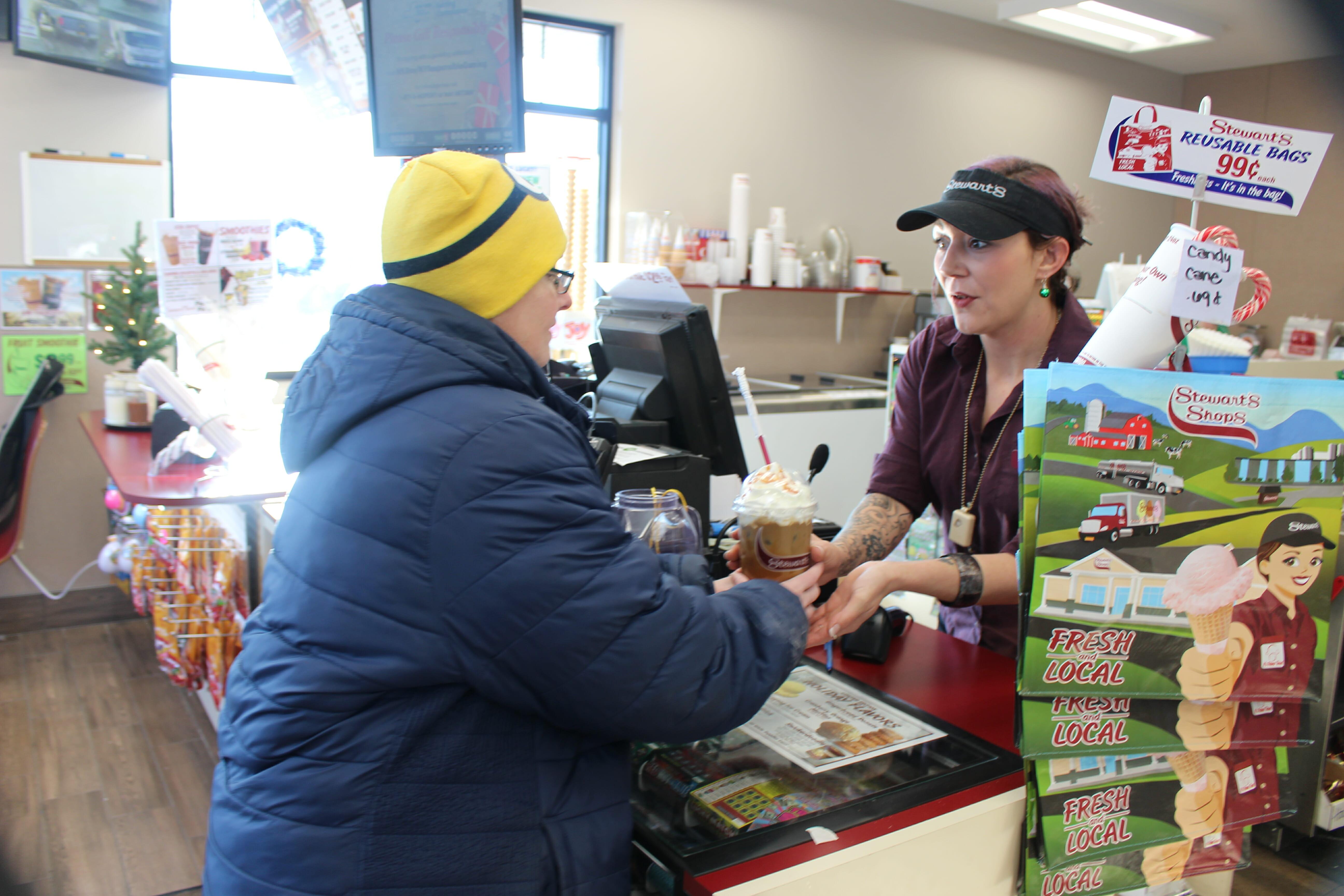 a stewarts partner handing an iced coffee to a customer