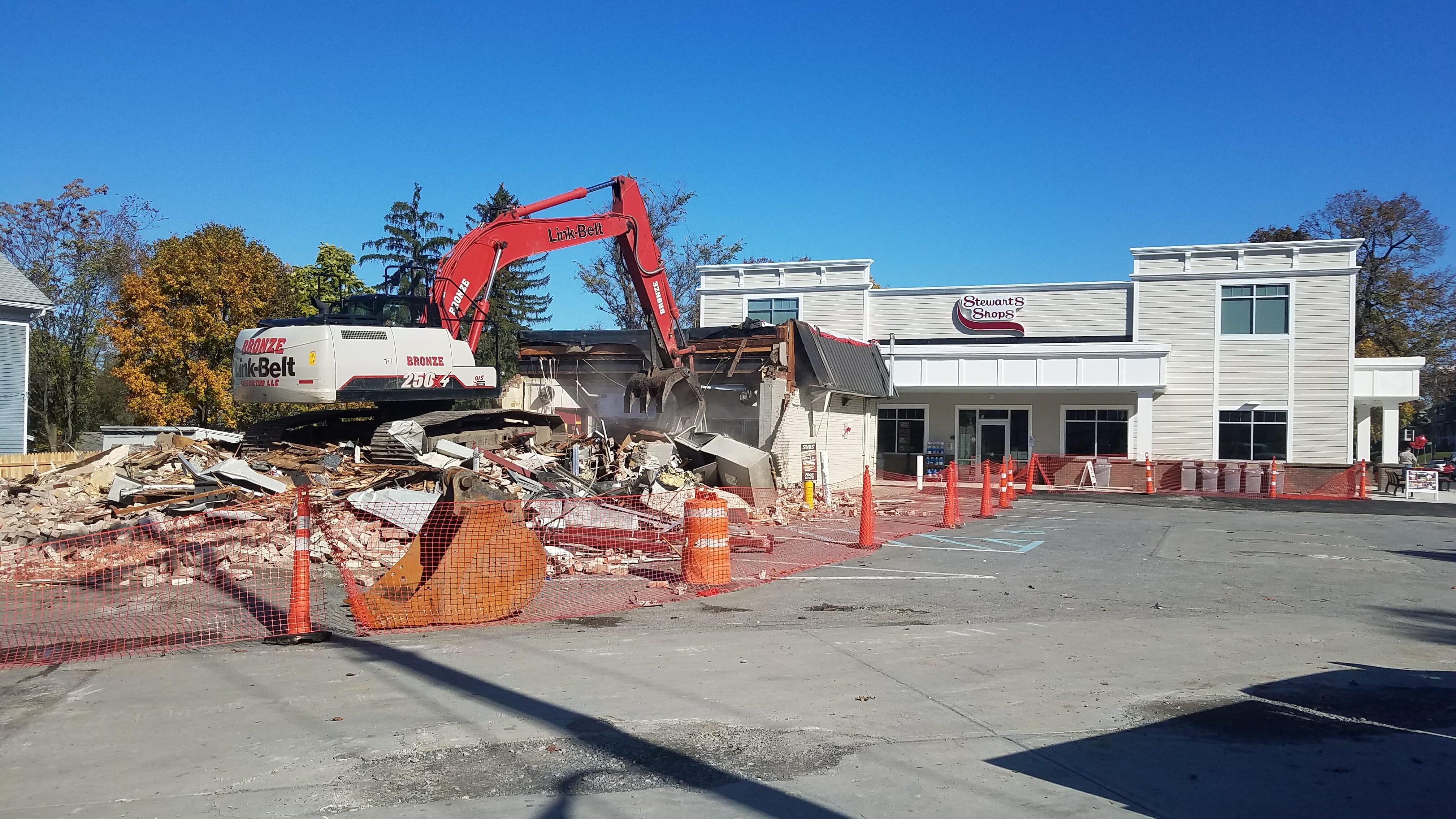 old stewart's shop being demolished by backhoe