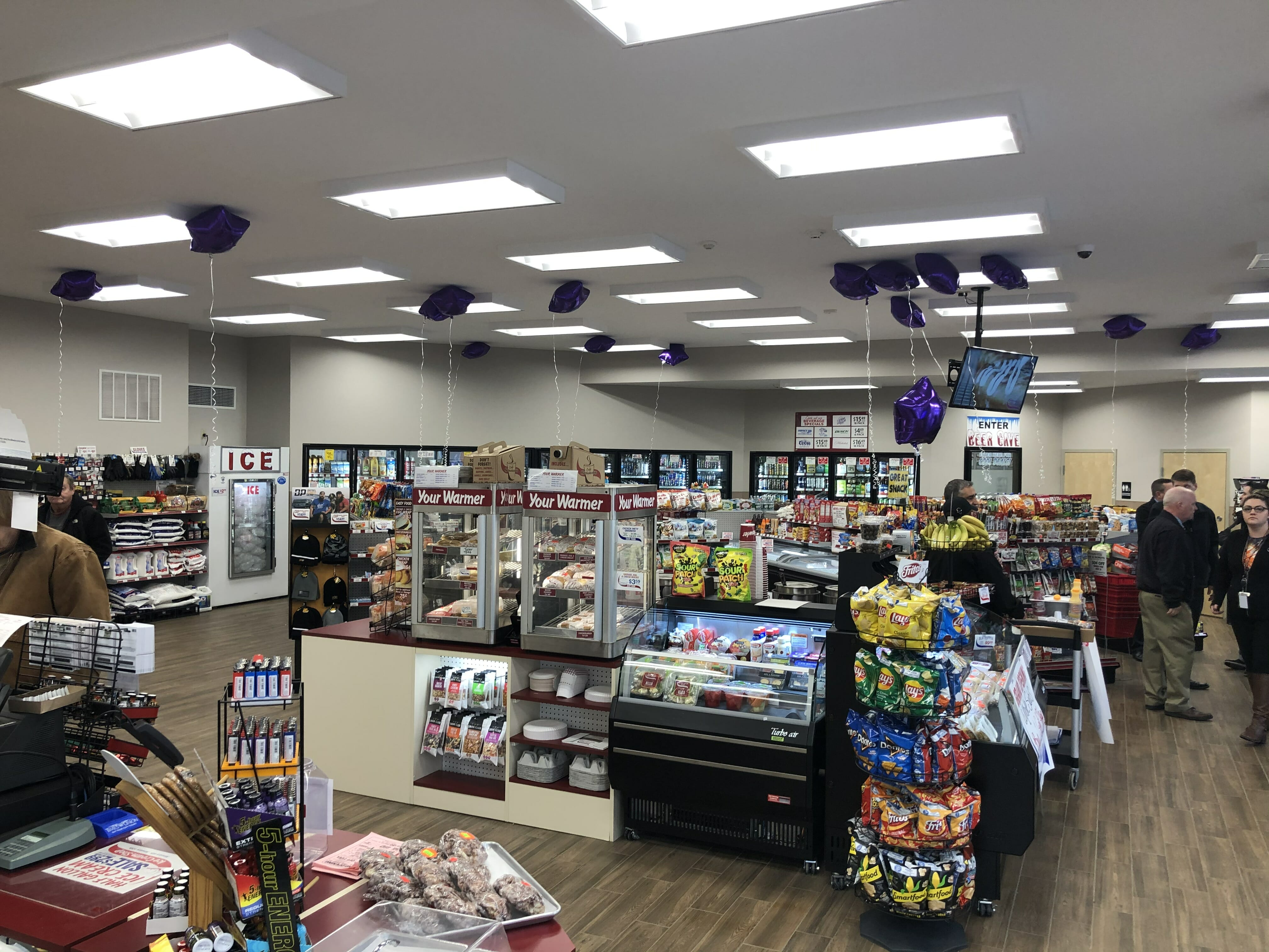 Inside the shop at the grand opening with balloons