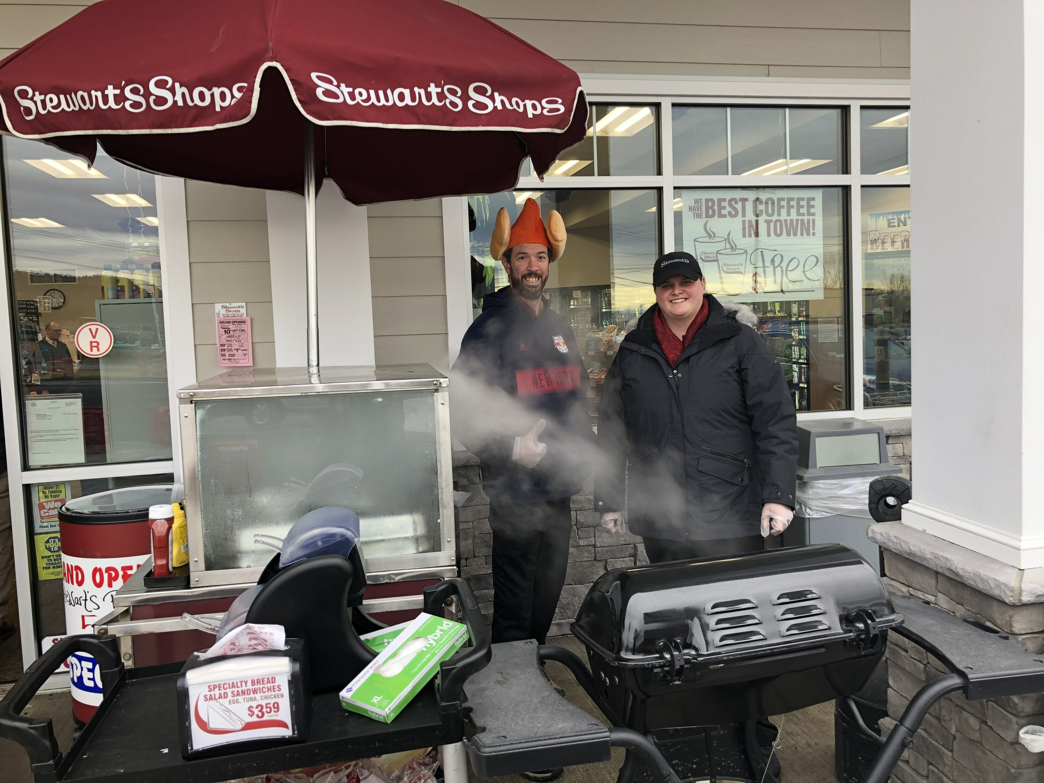 Selling hot dogs outside the shop at the event. Two employees, one wearing a hot dog hat