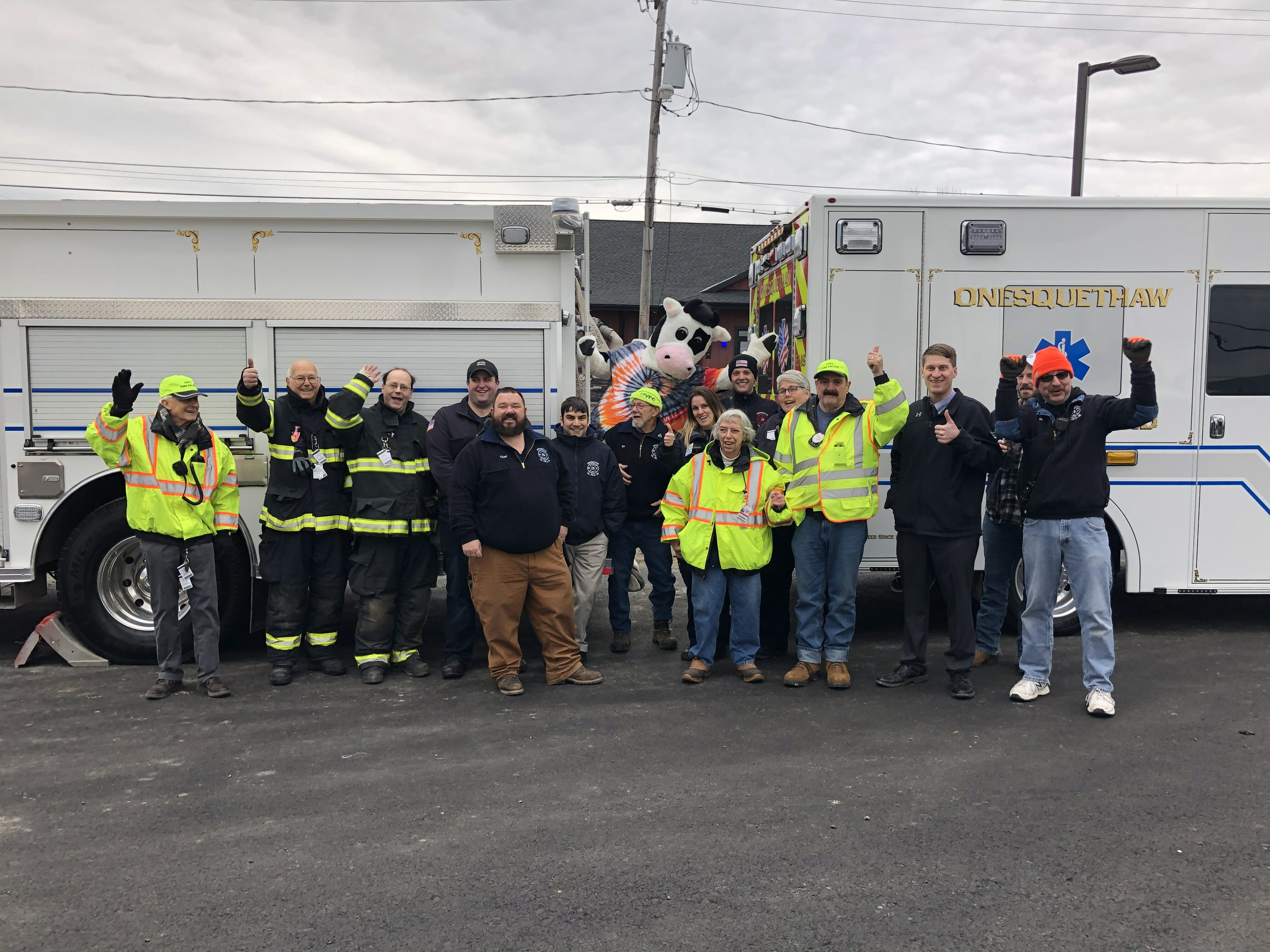 Group shot of the fire fighter crew with flavor the cow and two trucks