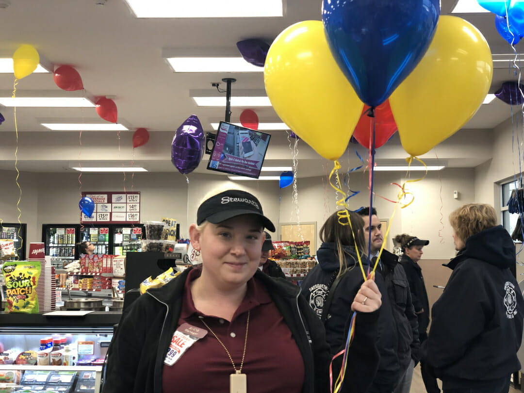 The manager holding balloons at the grand opening event
