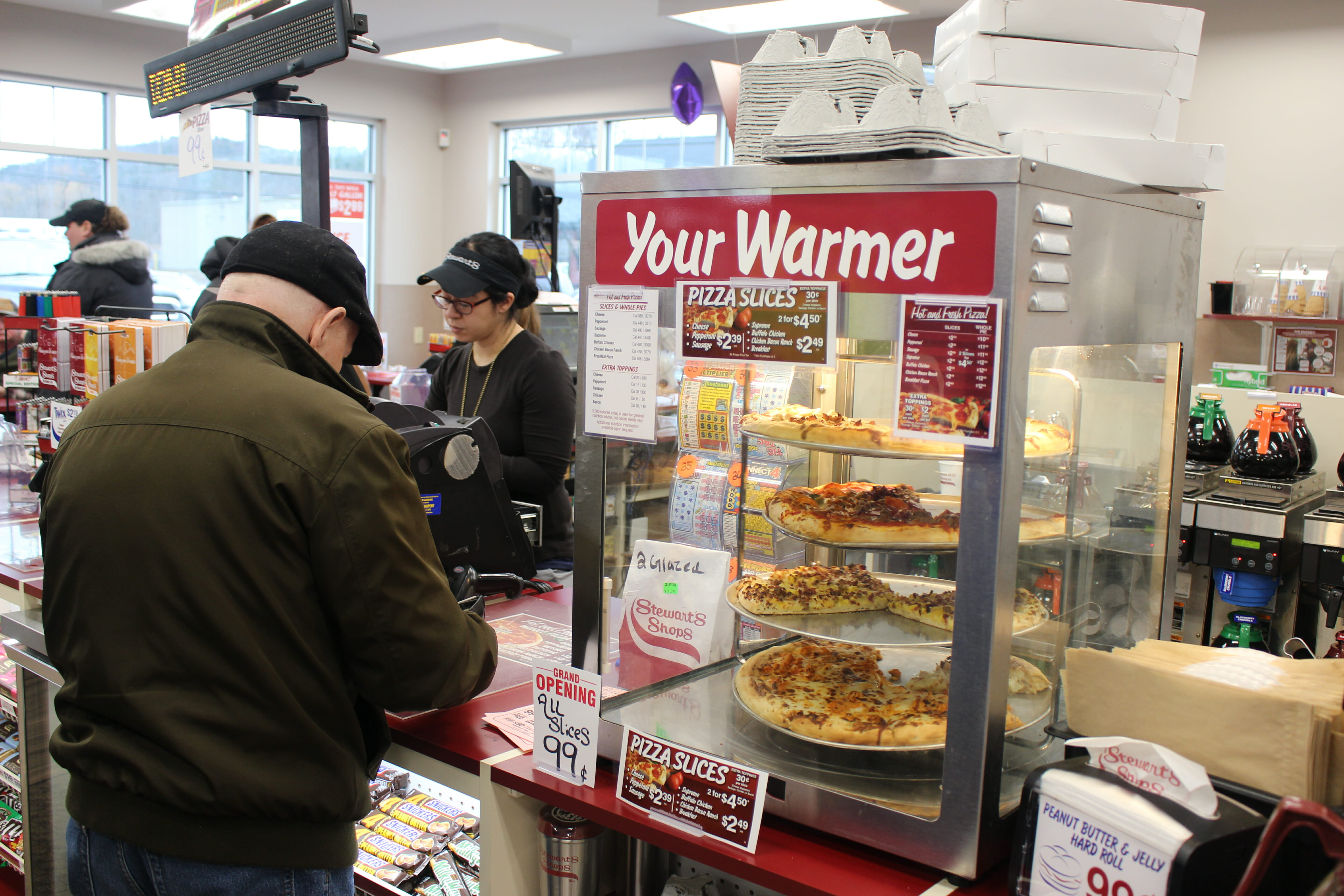 the pizza warmer full of pizza pies and a customer checking out at the new shop