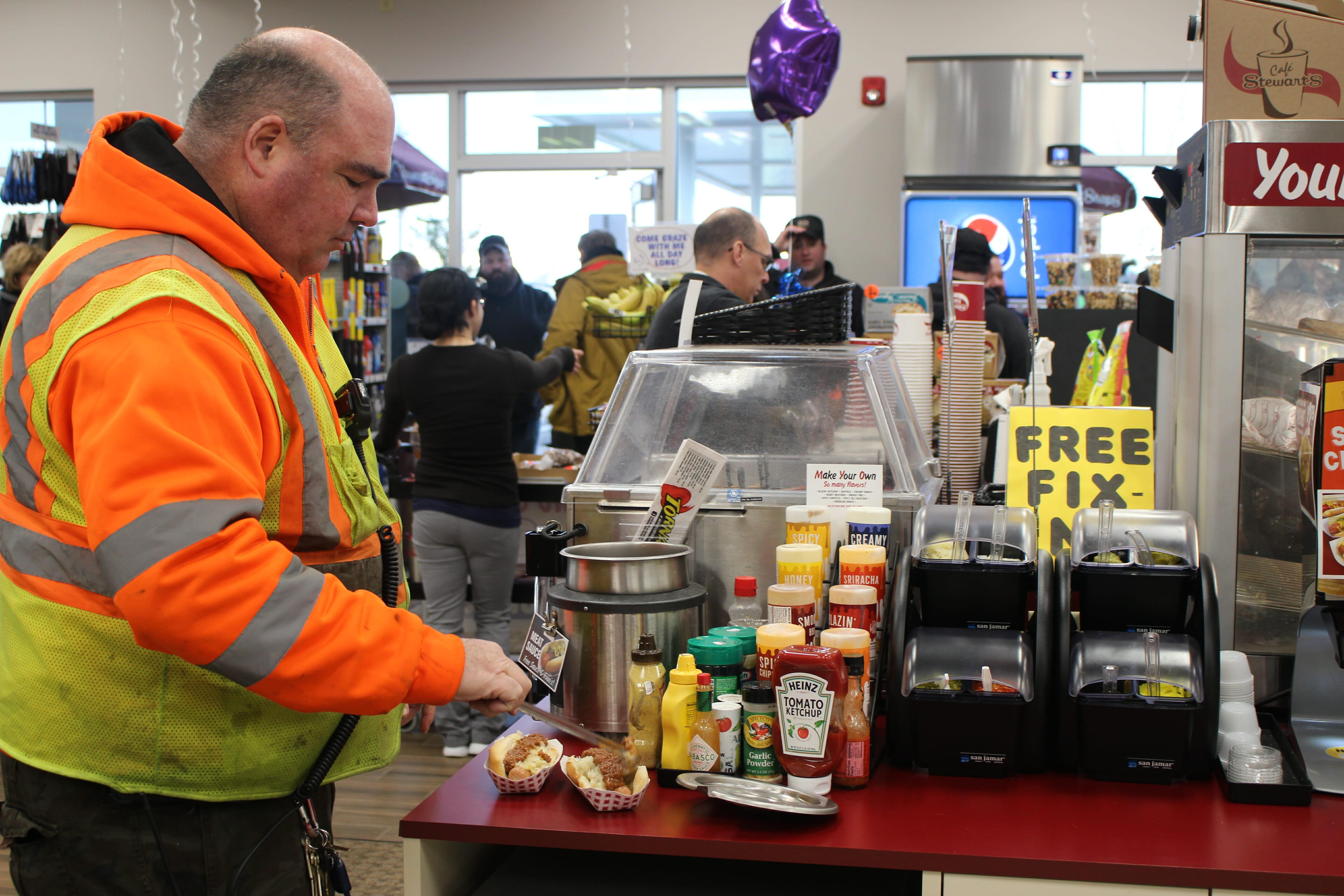 A man making a Make Your Own Hot Dog inside a Stewarts Shop