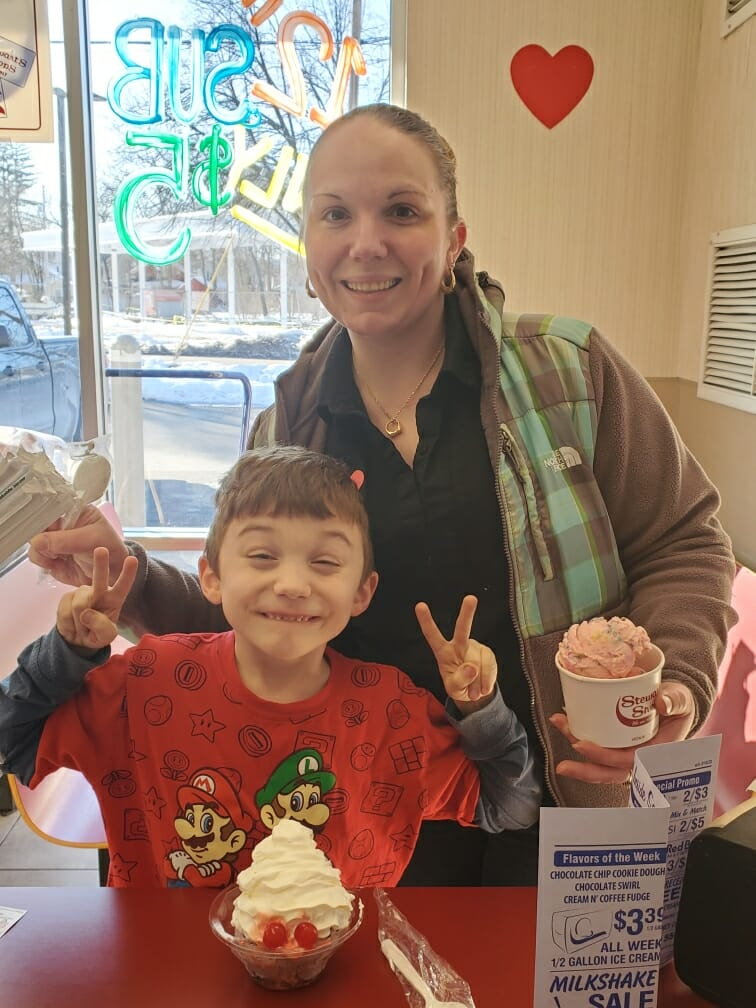A woman and a child posing for a photo with ice cream