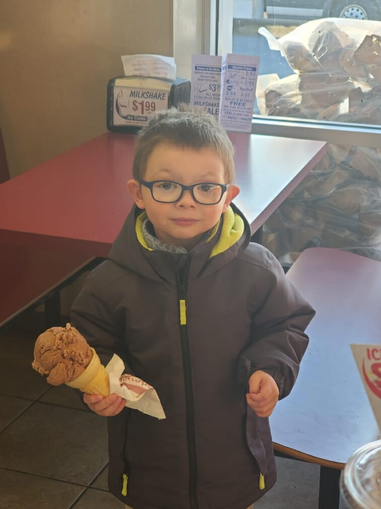 A little boy in glasses holding a chocolate ice cream cone