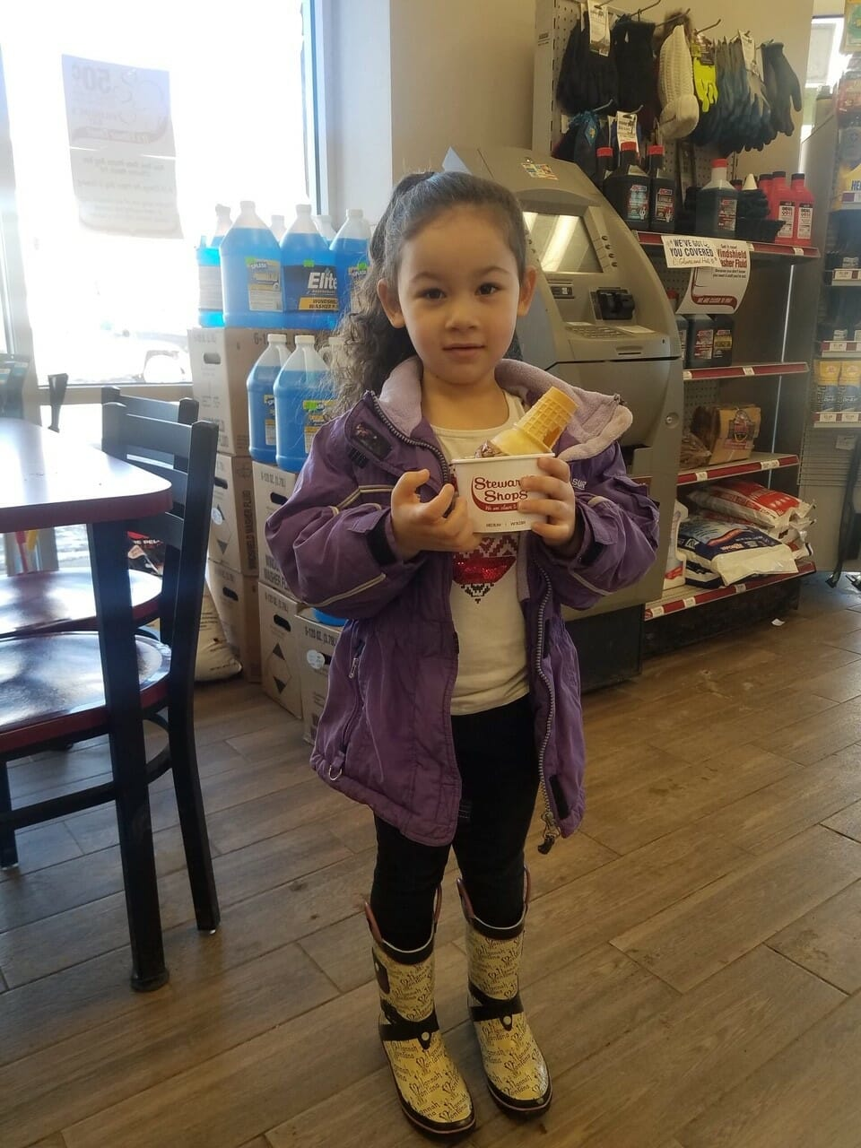 A little girl in a purple coat holding ice cream