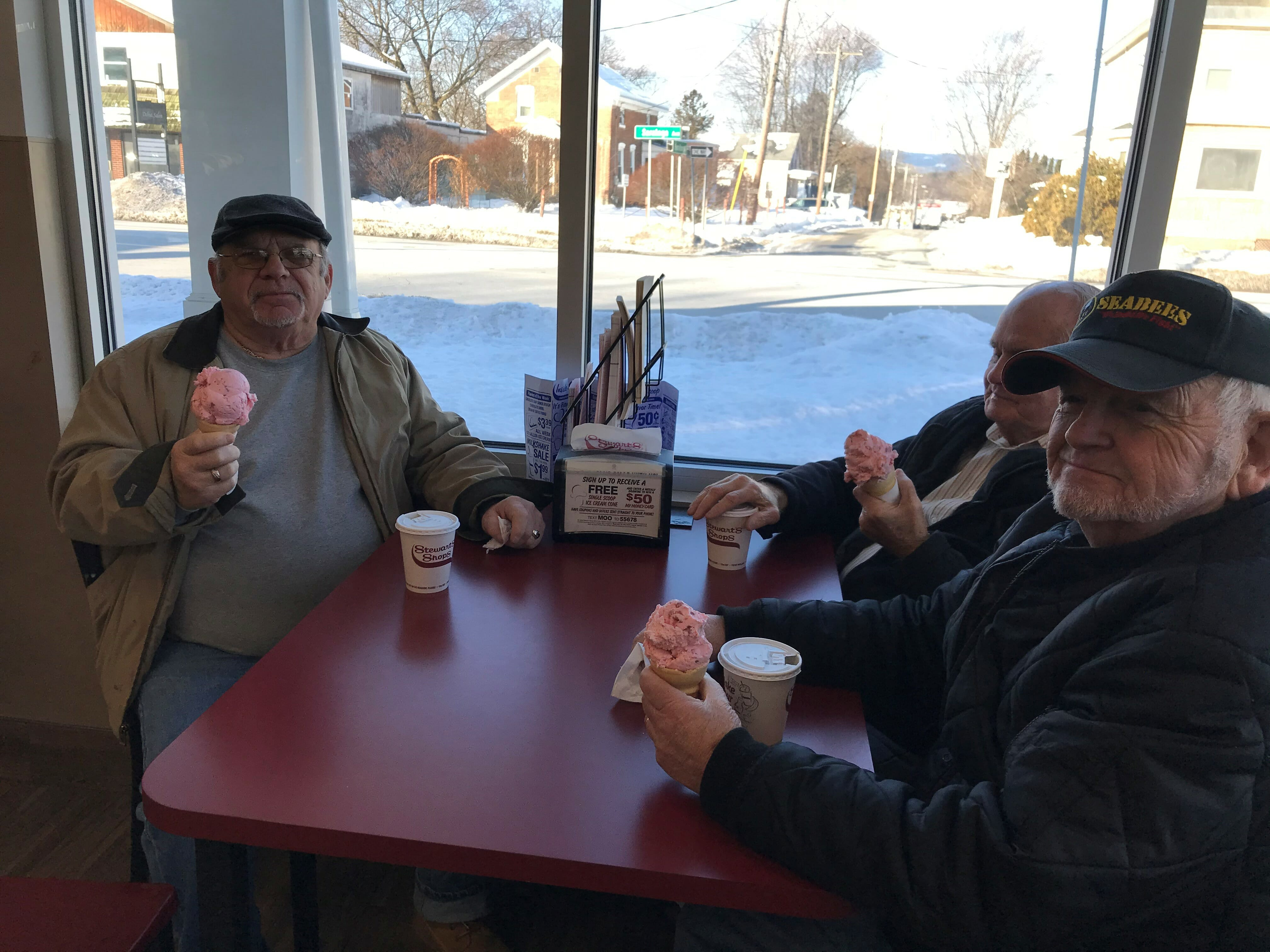 3 older men having ice cream together at a booth