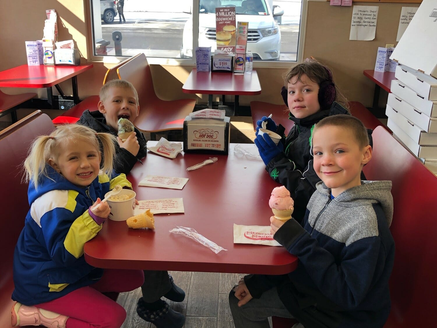 Four children sitting at a booth enjoying ice cream cones