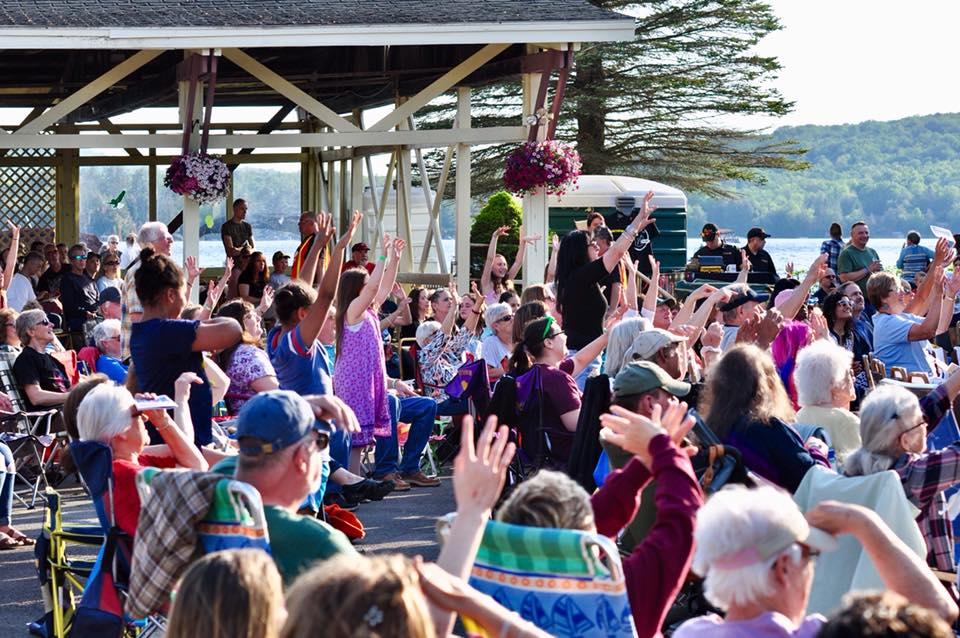 Crowd watches a music performance on the lake.