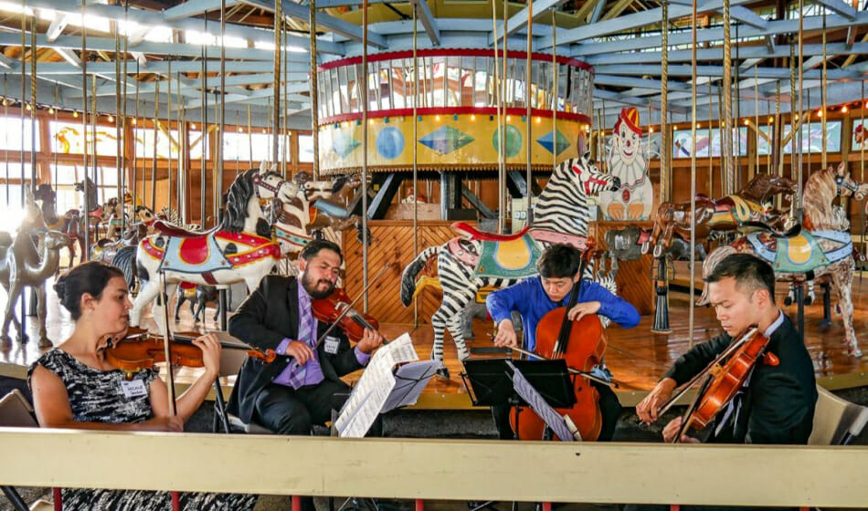 Violin Quartet in front of a carousel.