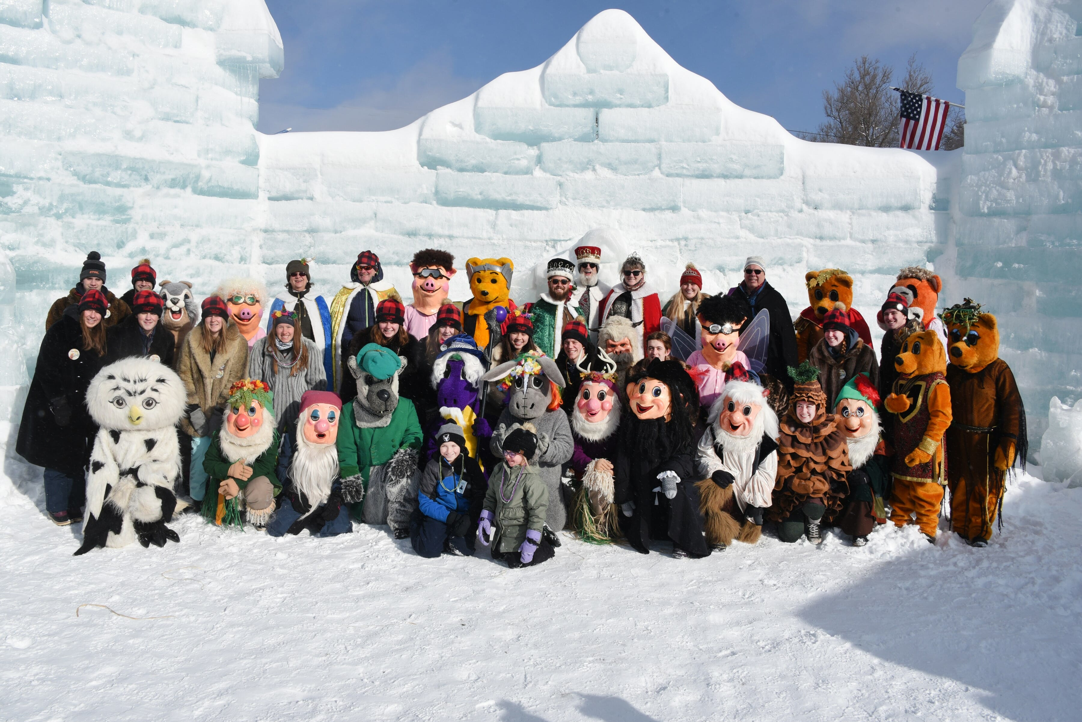 Costumed carnival characters in front of the ice palace.