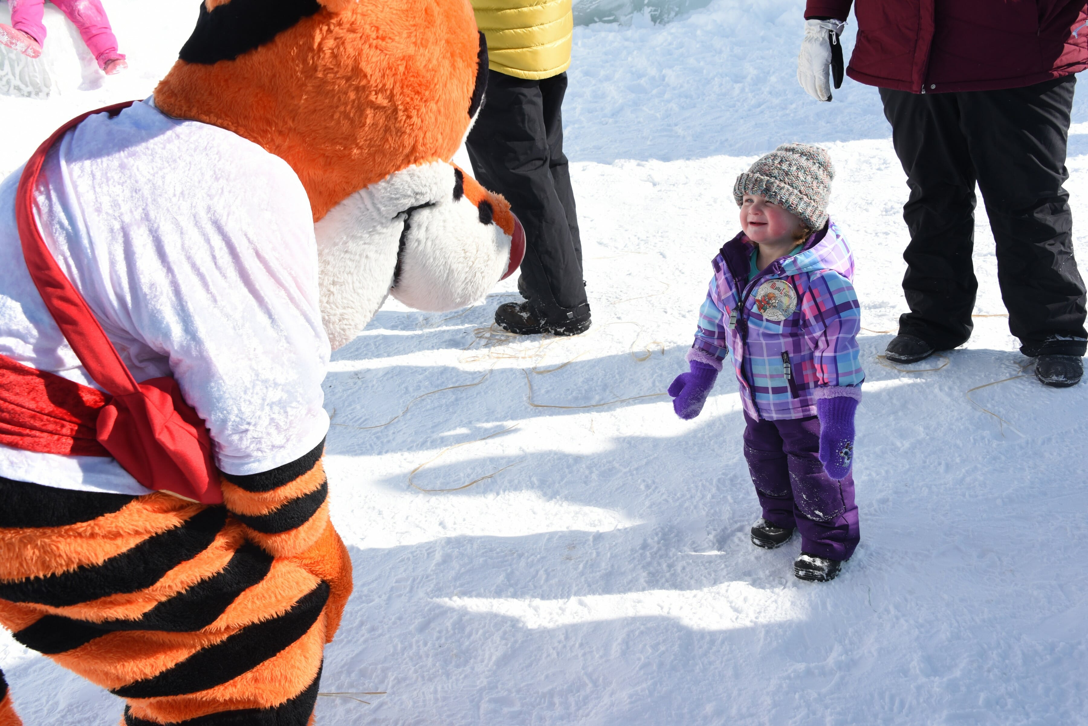 little girl greeted by a costumed character.