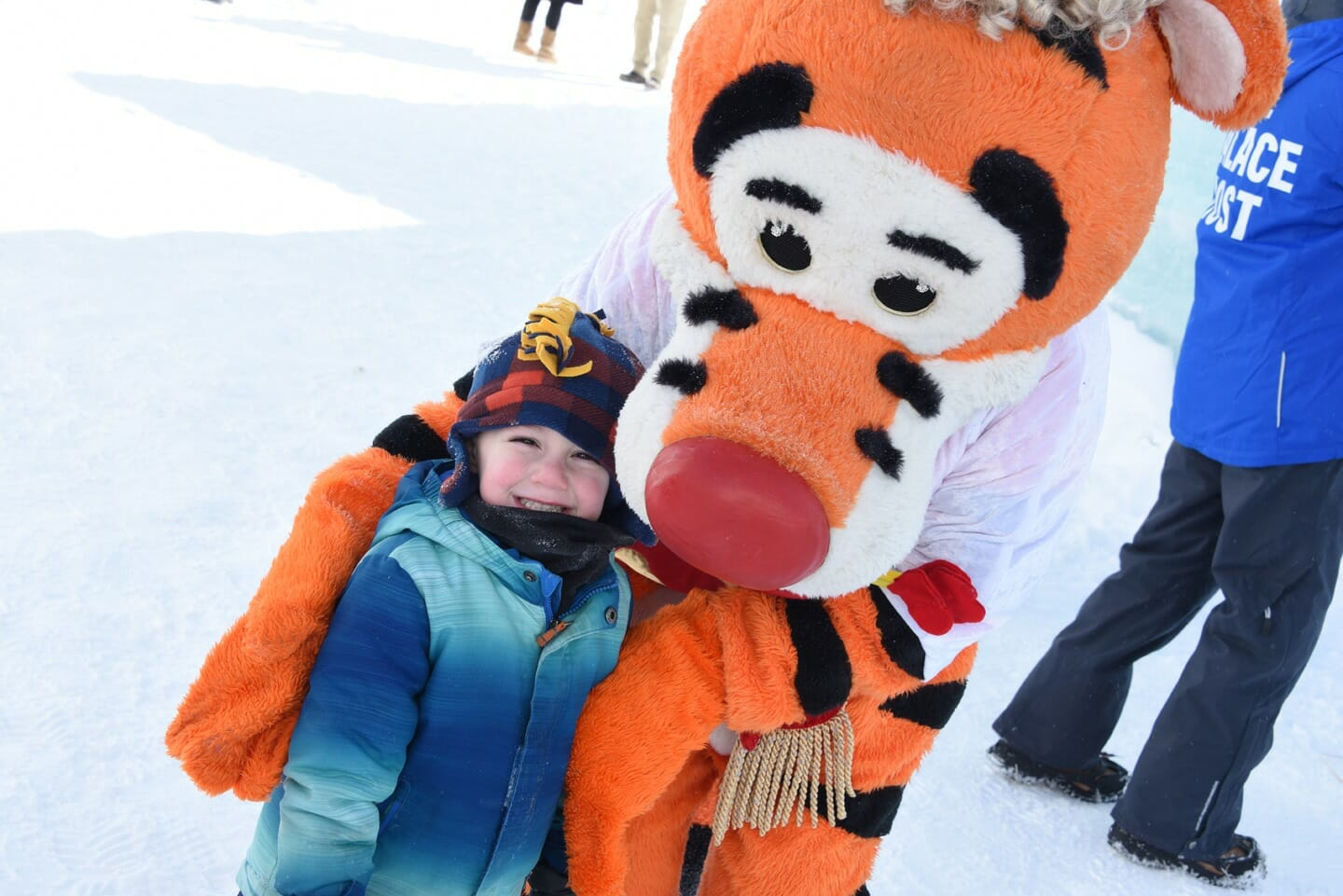 Child posing with a costumed character.