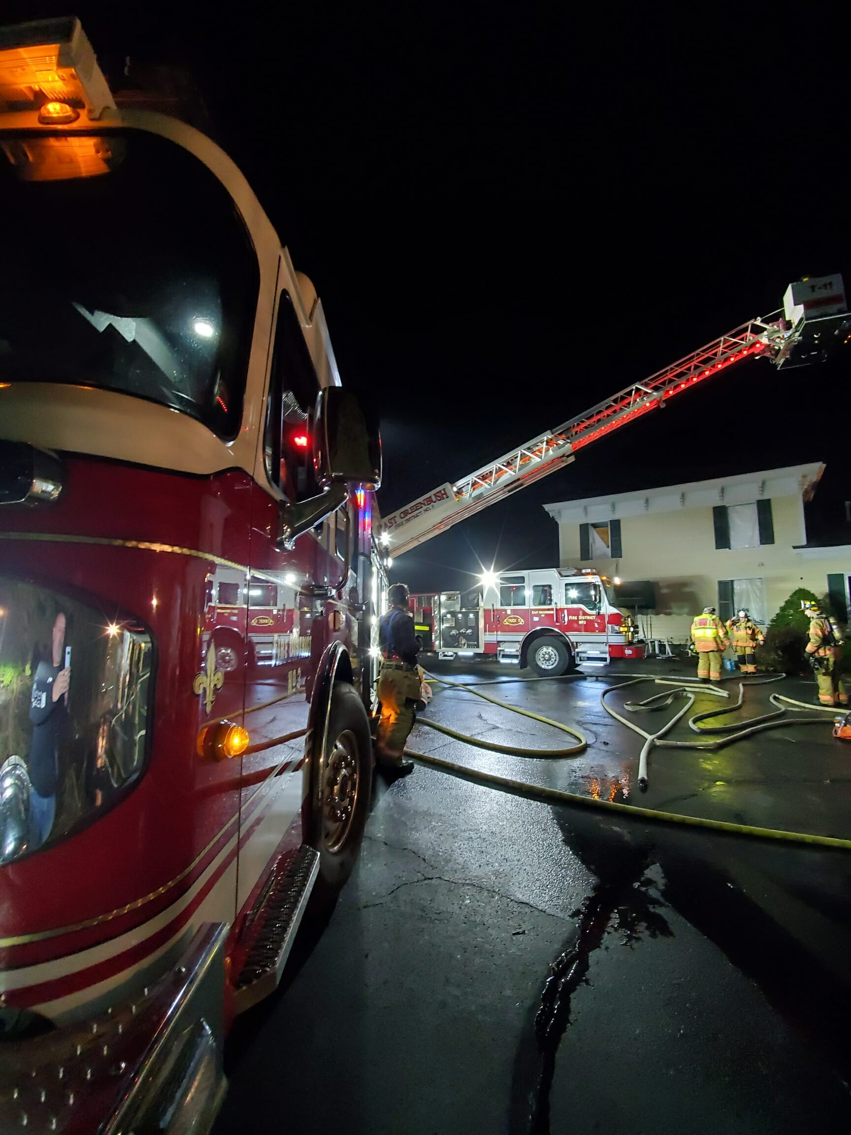Fire trucks at night. Firefighters in front of a yellow building
