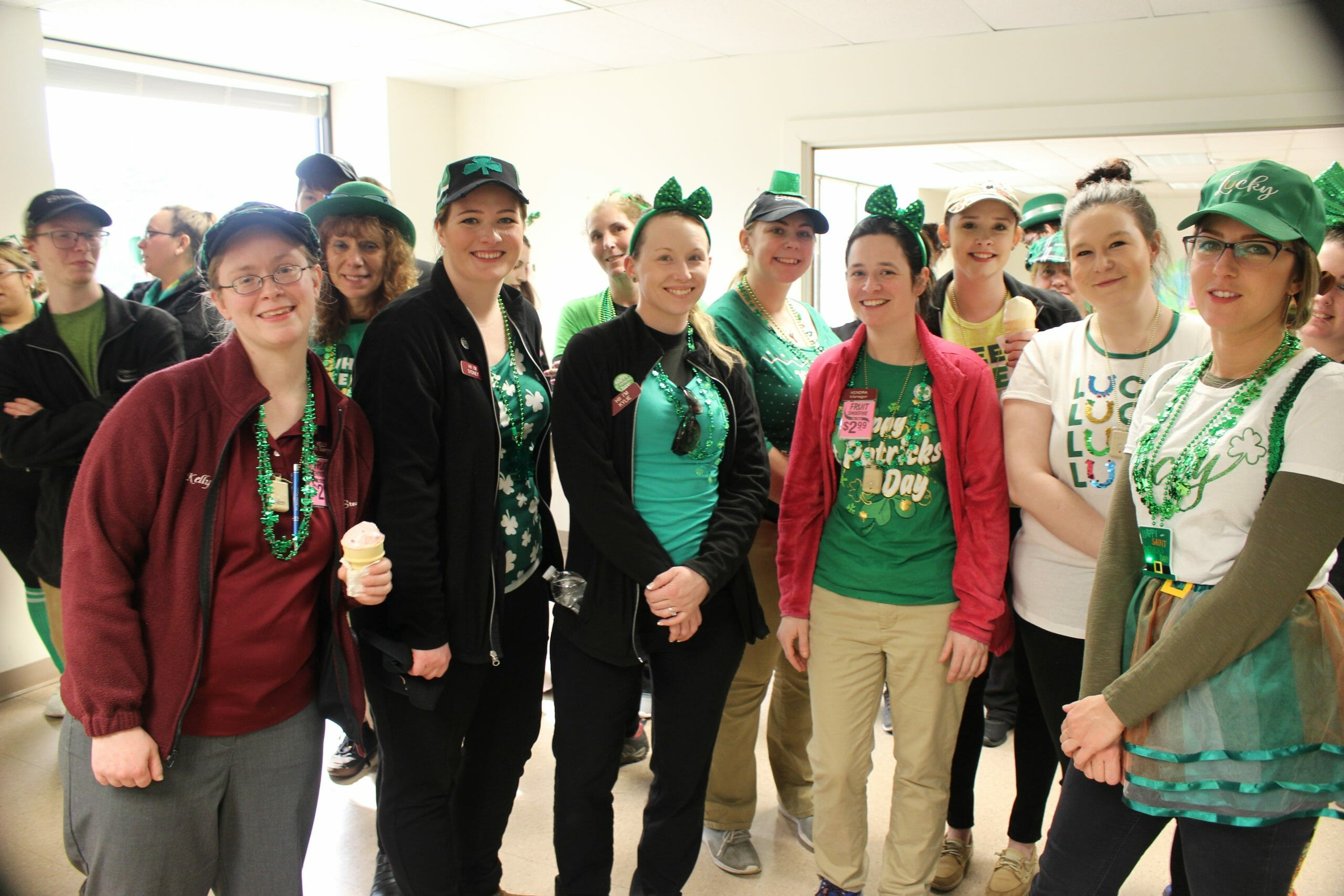 A group of partners dressed in green with st patricks day accessories