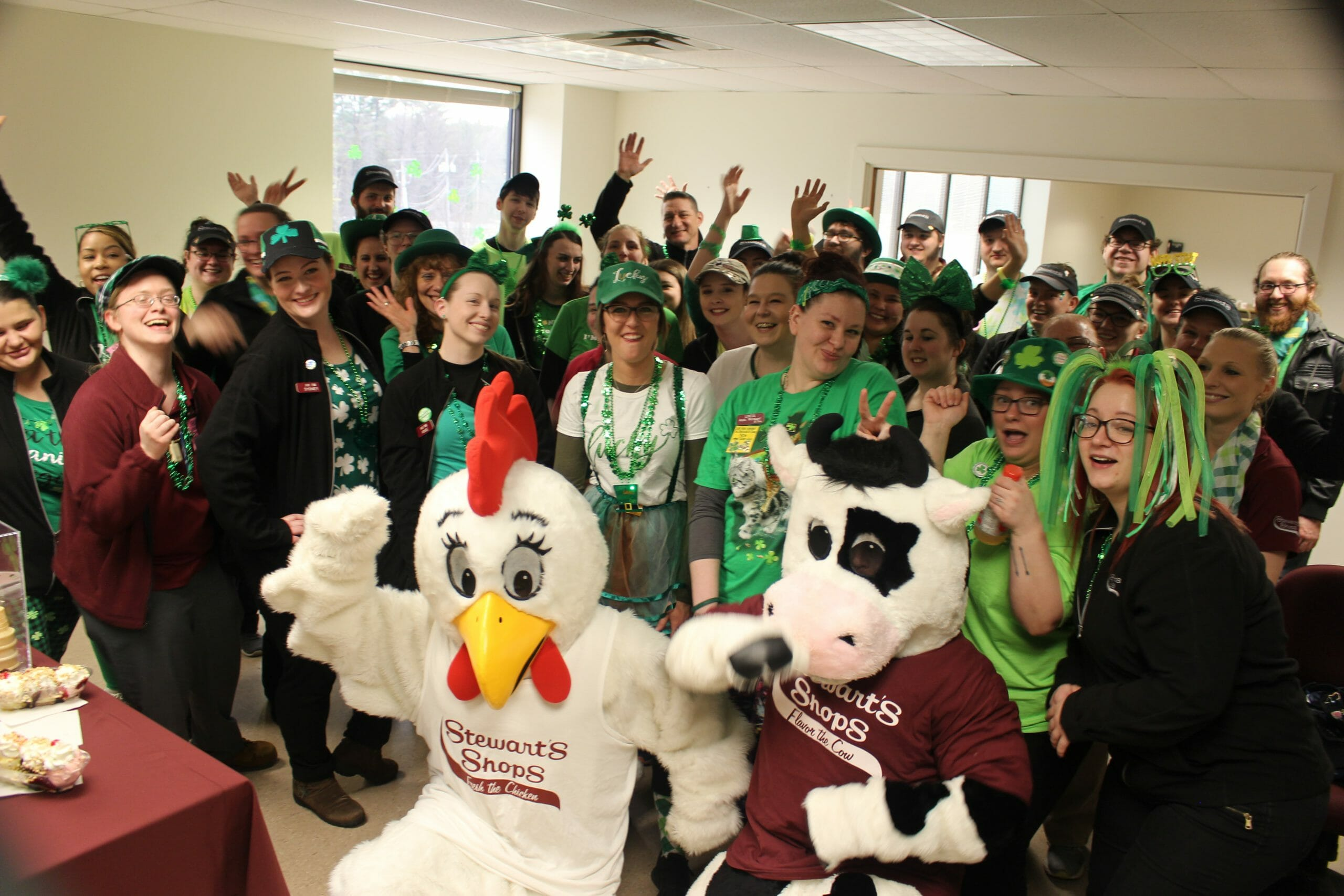 Group of Stewarts Partners and the mascots dressed in green