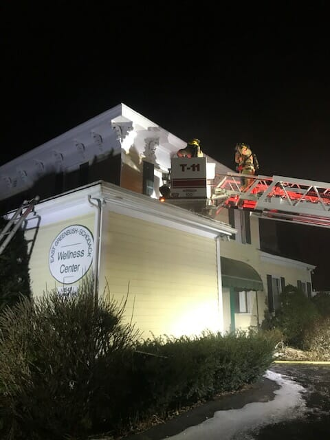 A building with a fire ladder extended to it with two firefighter