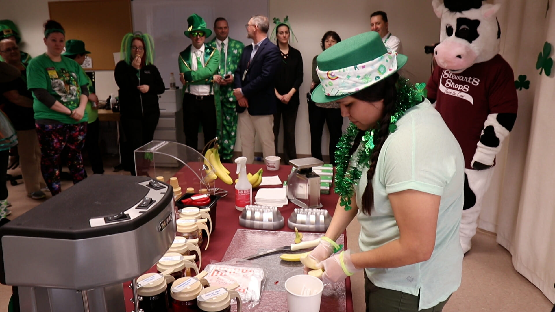 A partner slicing a banana to make a banana split at the dip off. People are in the background dressed up for st patricks day