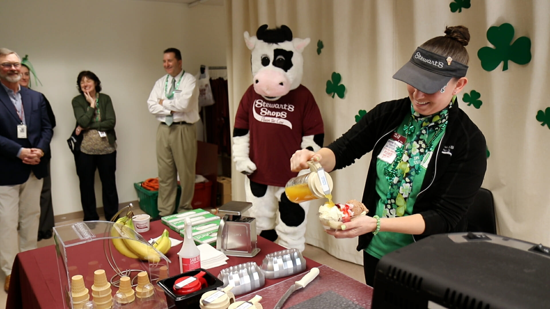 flavor the mascot watches a partner pour topping onto an ice cream sundae