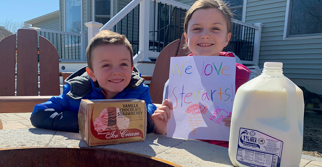 two kids a carton of ice cream and a gallon of milk. The little girl is holding a sign that says We Love Stewarts thank you with an ice cream cone