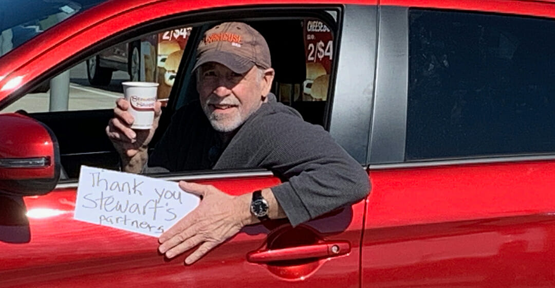 A man in a red car holding a coffee and a sign that says thank you stewarts partners