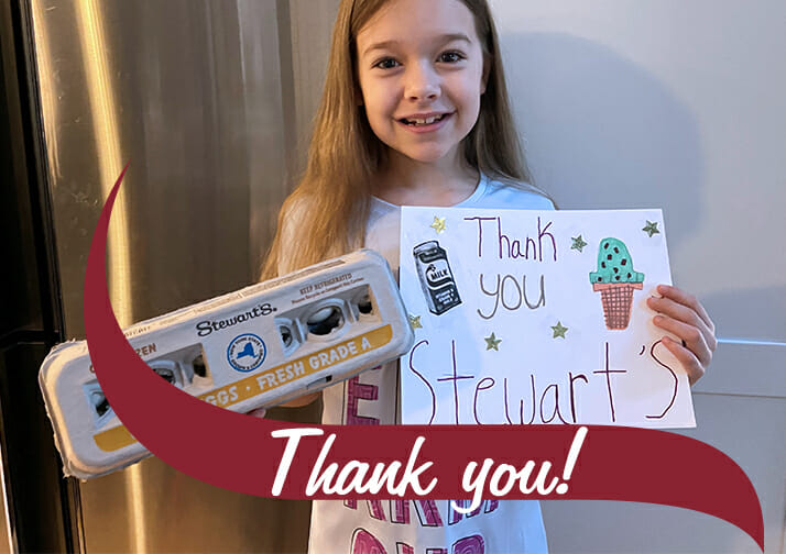 A little girl holding eggs and a sign that says thank you Stewarts. Thank you