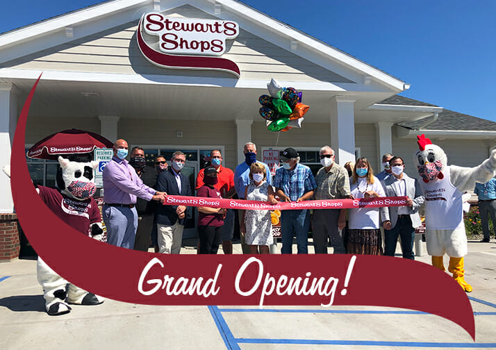 Group image of the ribbon cutting in front of the Port Henry shop. Grand Opening!