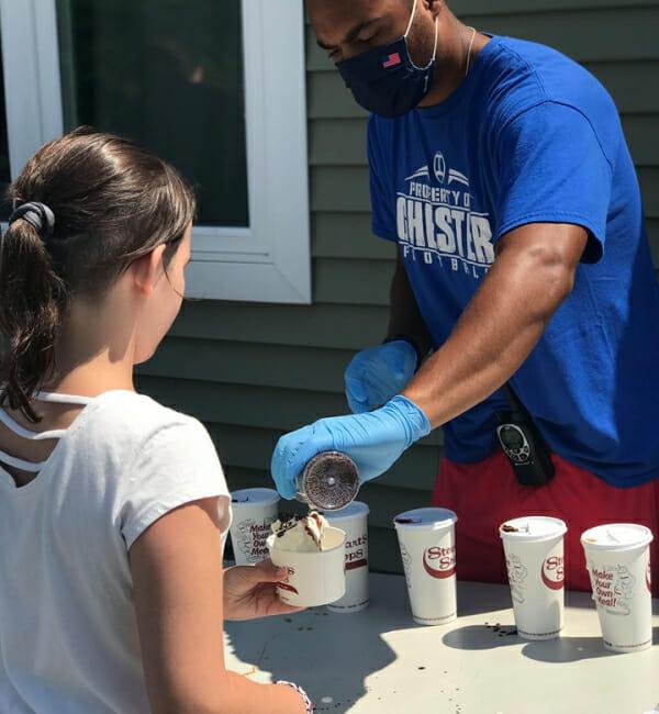 Volunteer scooping ice cream with camper.