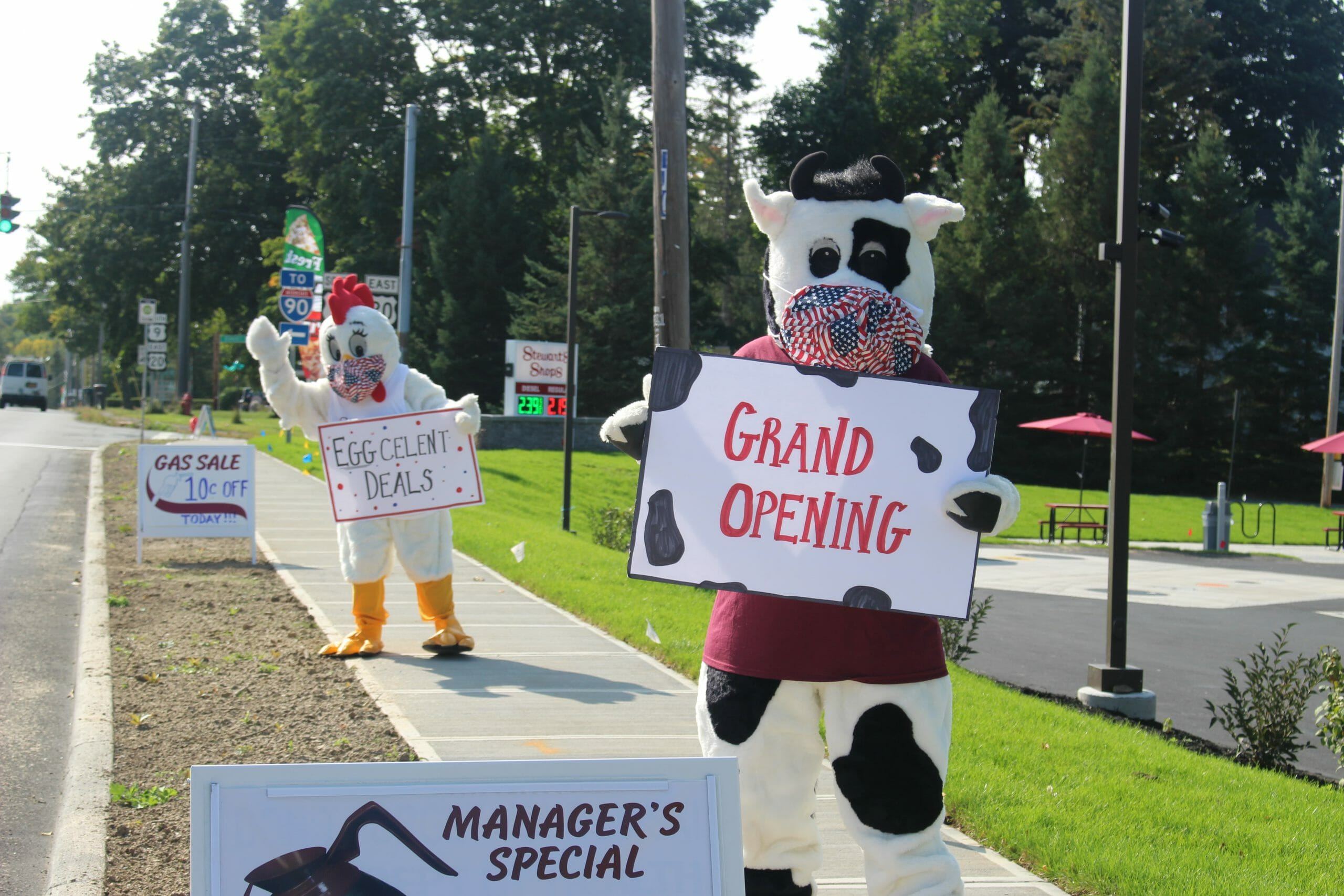 The Stewarts mascots Fresh the chicken and Flavor the Cow holding signs Eggcelent deals and Grand opening