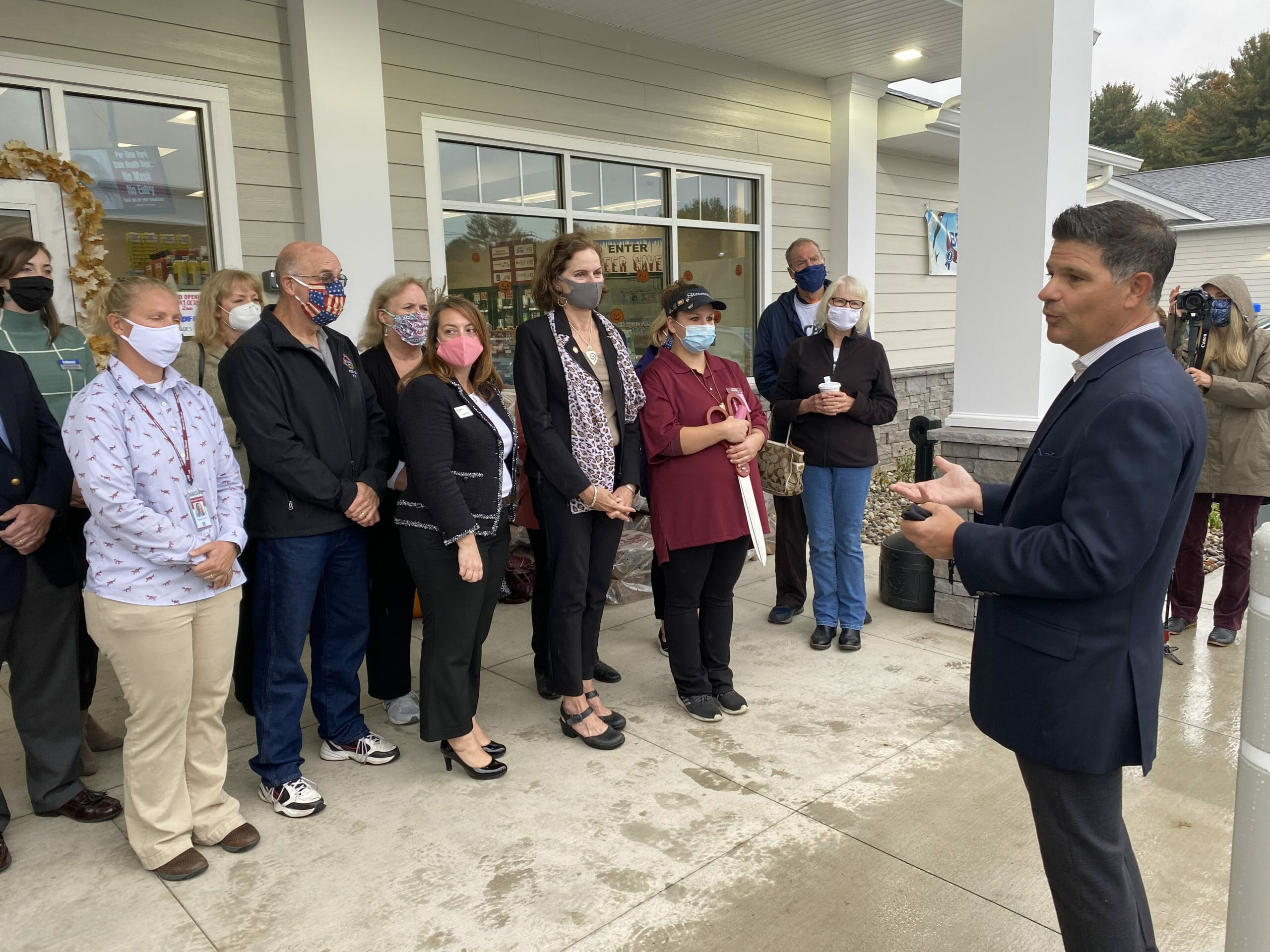 council man speaking in front of new karner shop
