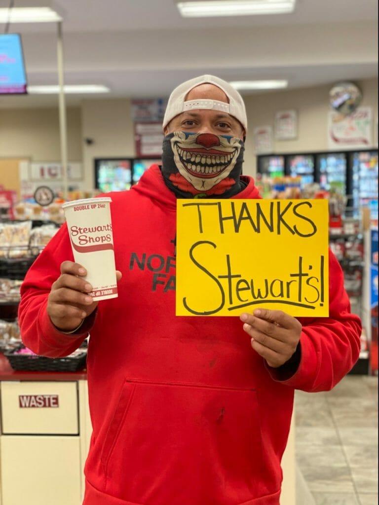 Man in red sweatshirt holding thanks stewart's sign