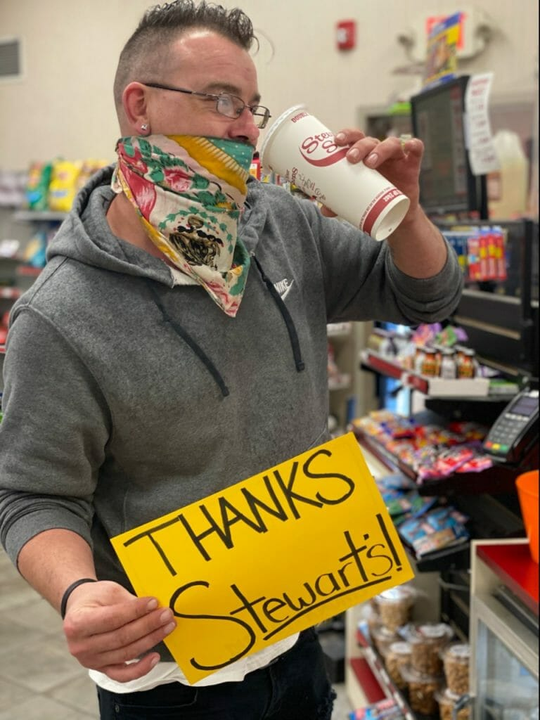 Man holding Thanks Stewart's Sign while pretending to drink coffee