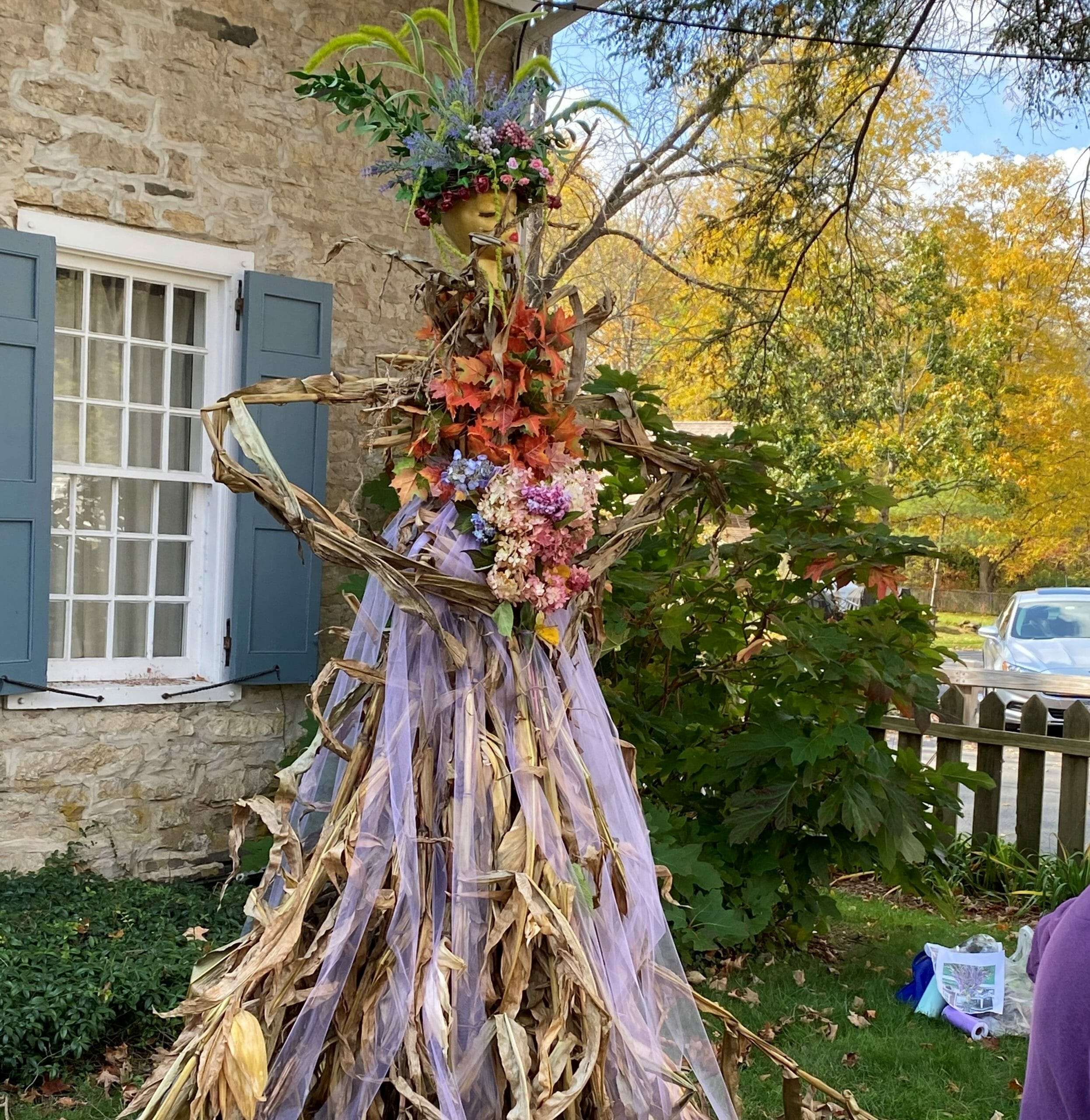 Scarecrow hold bouquet of flowers