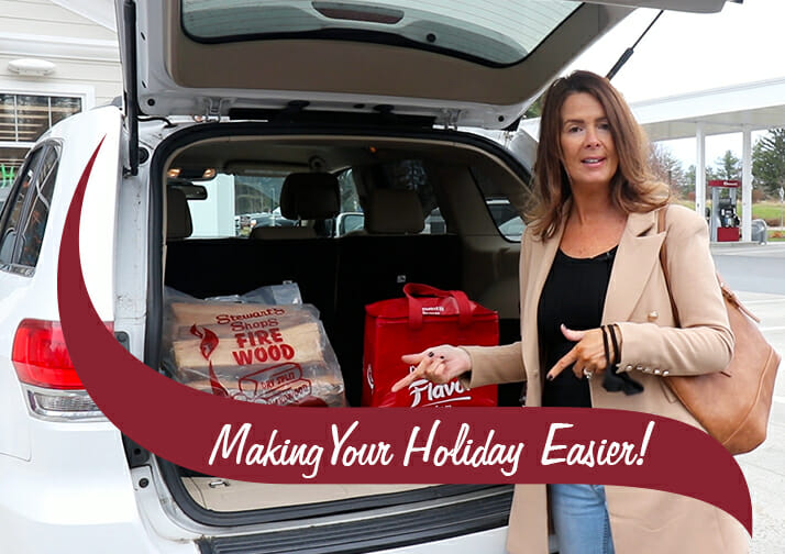 A woman packing her car trunk with firewood and a bag. Making Your Holiday Easier