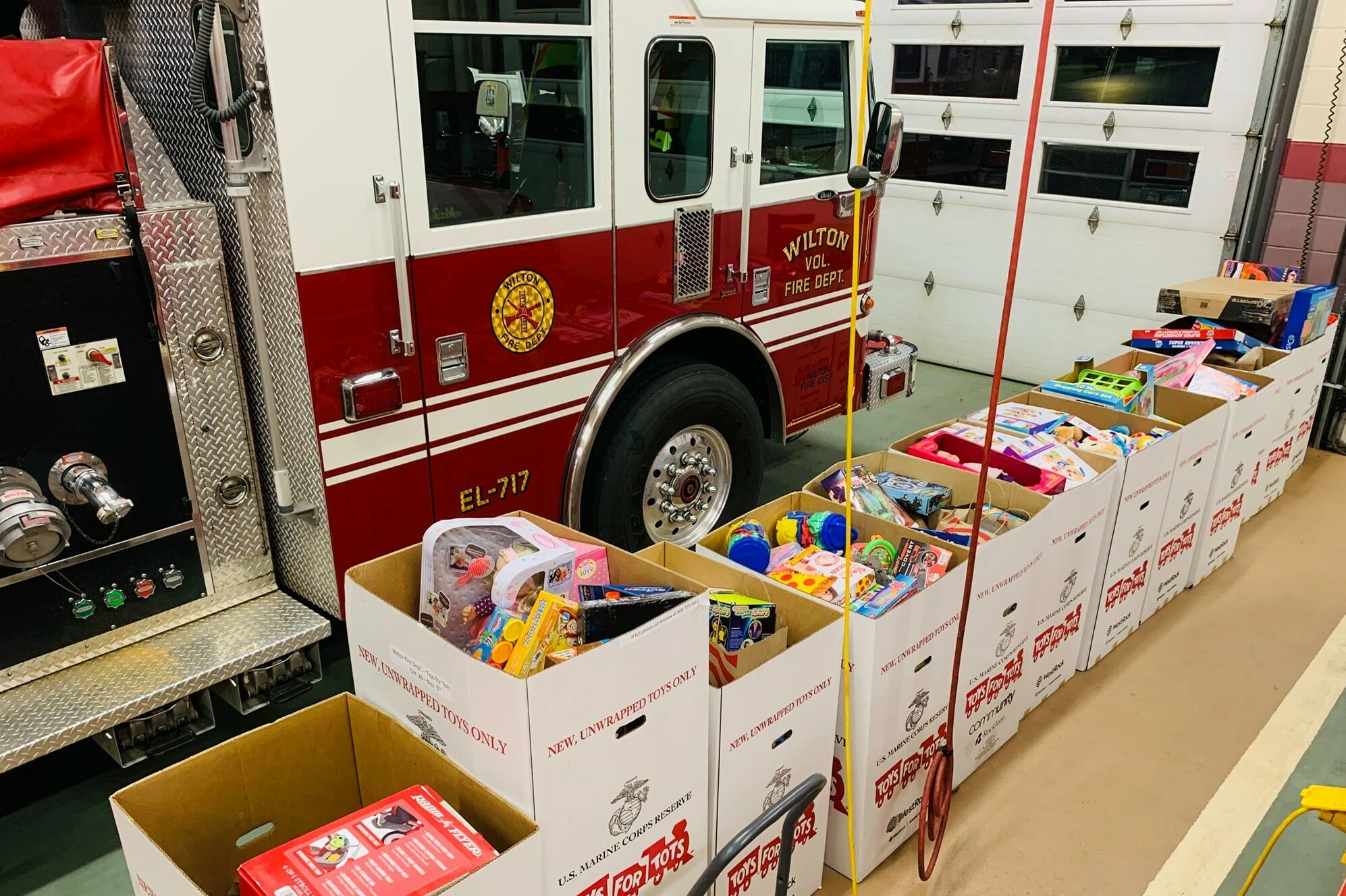 Toys for tots boxes in front of a firetruck.