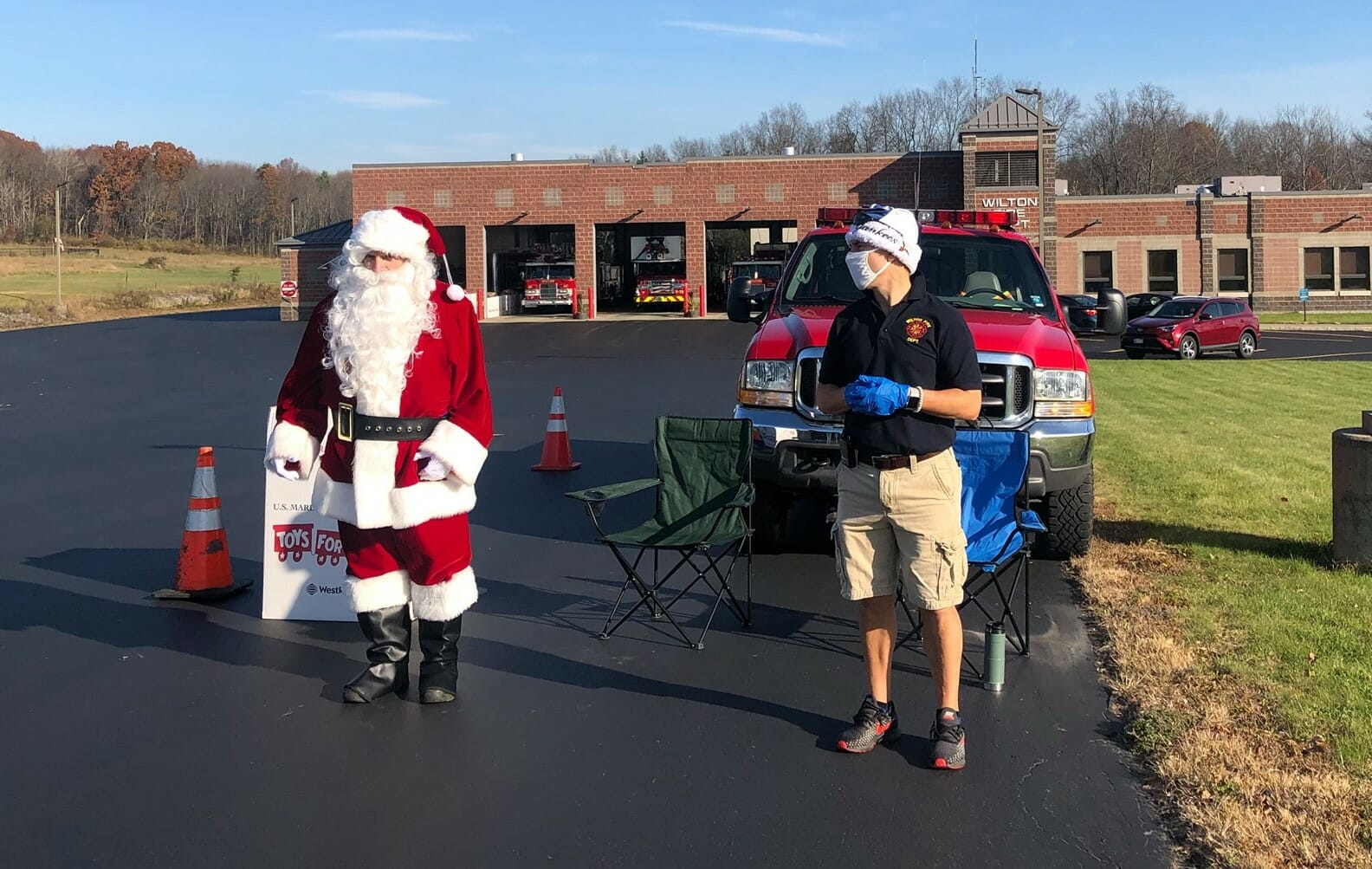 Santa and a fire department worker waiting to greet kids.