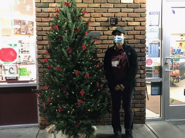 Partner with a mask posing with our Christmas tree