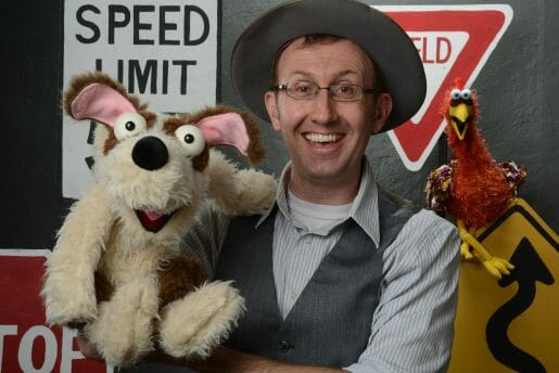 The Mesner Puppet Theater actor posing with a dog and chicken puppet.
