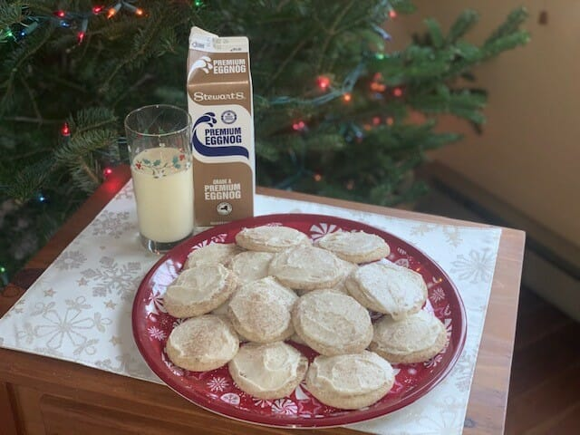 Plate of eggnog snickerdoodles with a carton and glass of Eggnog